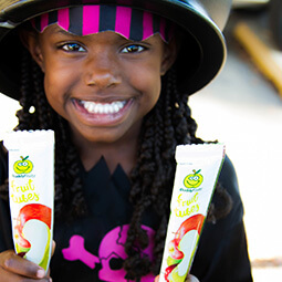 Afro-american girl smiling Halloween costume funny snack buddy fruits UGC content