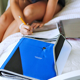 girl studying bed pencil writing notes holding binder blue school college branded UGC content