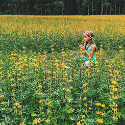 girl field flowers yellow green travel UGC content